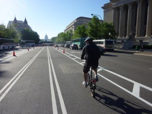 Lone bicyclist on Pennsylvania Avenue bike lane in early morning; buses queued in background