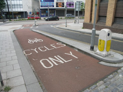 Barrier-separated bikeway with colored pavement, Bristol, England. Photo by James Mackay