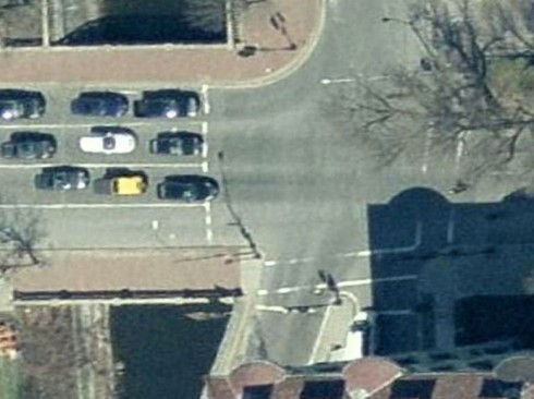 "Intersection of Commonwealth Avenue and Charlesgate West before the additional of a bike lane (Microsoft Bing aerial view). Though there is an arrow indicating that the right lane is for through travel, it is unused, because it leads to a row of parked cars in the next block. It is a ""musical chairs"" lane."